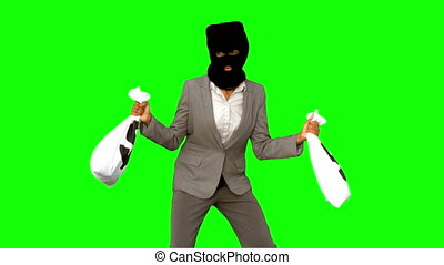 Burglar wearing balaclava and holding money bags on green...