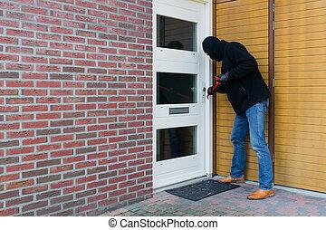 Burglar with a crowbar - Mean looking burglar enters a house