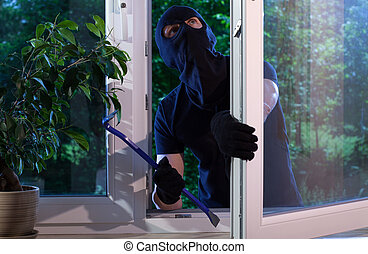 Burglar with crowbar breaking into the house