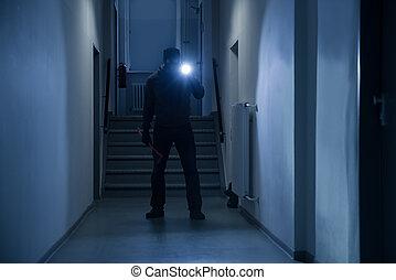 Full length of burglar with flashlight and crowbar in office corridor