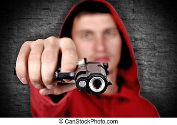 burglar with gun on a gray background