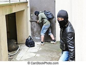 Burglary. One burglar tries open the door. Second is on the...