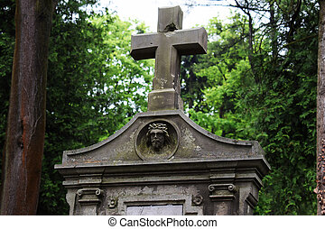 Burial vault in the cemetery, a large stone cross, the image of Jesus on the burial vault