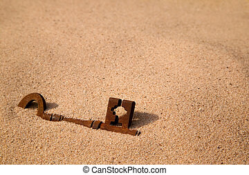 A rusty old key buried in the sand