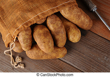 A overhead view of a burlap sack of potatoes on a rustic wooden background. Horizontal format with copy space.