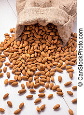 Burlap sack with almonds spilling out