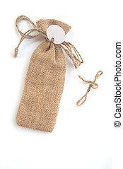 burlap sack with tag on white, souvenir in wedding