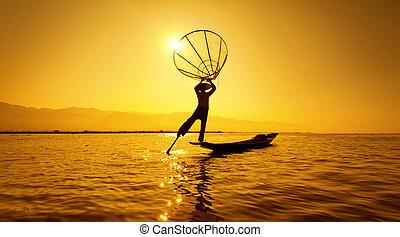 Burma Myanmar Inle lake fisherman on boat catching fish by...