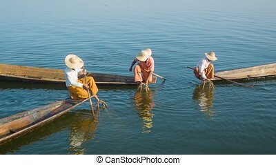 Burmese fishermen on Inle Lake with traditional fish traps -...