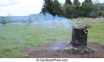 Burn Barrel - An old barrel with rubbish and sticks burning...