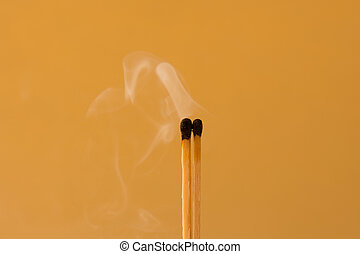 Burn out matches against an orange background