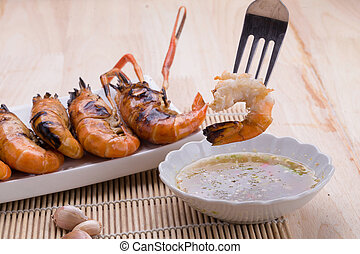 Burn shrim and Seafood sauce on wooden table.