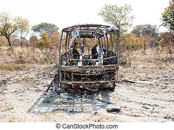 Burned bus at the side of the road