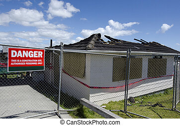 Burned house - A sign reads - DANGER outside a wood framed...