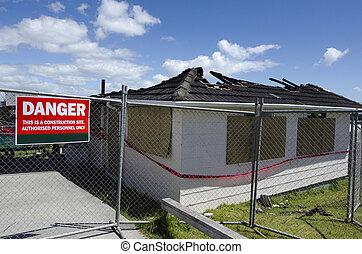 Burned house - A sign reads - DANGER outside a wood framed...