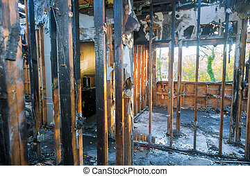 Burned house interior after fire burnt black timber roof structure building room inside