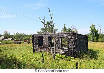 burned rural house on green field
