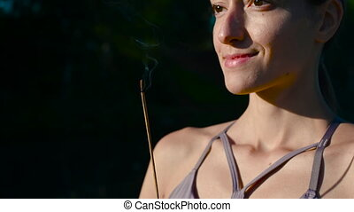 Burning aromatic sticks for meditation while doing yoga outdoors at forest lake