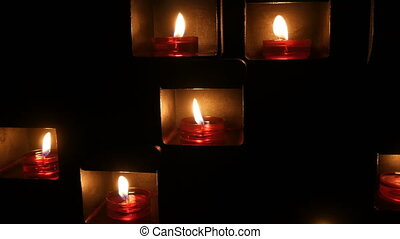Burning beautiful red round prayer candles in a special niche in the darkness of a Catholic church.