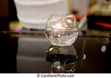 Burning beeswax candle in crystal bowl decoration in room