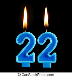 Burning birthday candles in the form of 22 twenty two for cake isolated on black background.