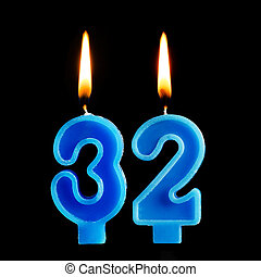 Burning birthday candles in the form of 32 thirty two for cake isolated on black background.