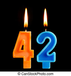 Burning birthday candles in the form of 42 forty two for cake isolated on black background.