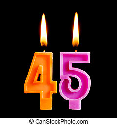 Burning birthday candles in the form of 45 forty five figures for cake isolated on black background. The concept of celebrating a birthday, anniversary, important date, holiday