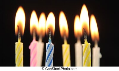 Burning birthday candles on black background