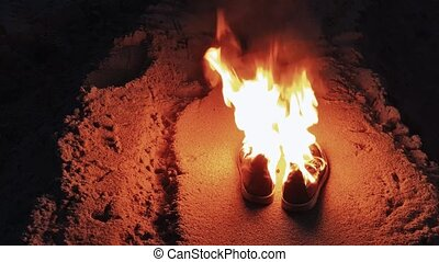 Burning boots on the sand at coast