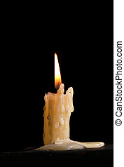 Burning candle against a black background