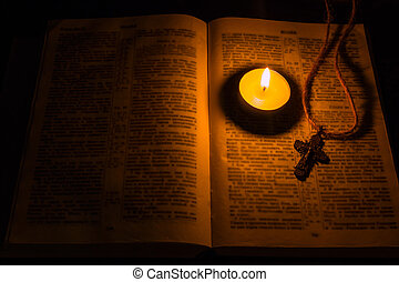 burning candle and a cross on bible Selective focus