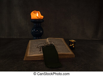 Burning candle and an open old book