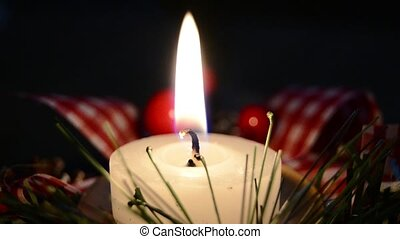 Burning candle and Christmas decoration over snow and wooden...