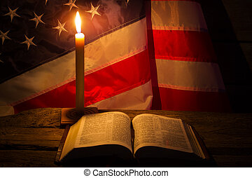 Burning candle and open book. America's flag behind burning...