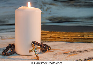 Burning candle and rosary with crucifix cross.