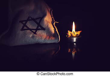 burning candle and the Star of David against a black...