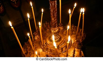 Burning candle closeup on the background of other candles in the Christian Orthodox Church