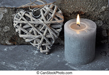 Burning candle, heart and wood billet on concrete