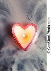 burning candle heart in dense fog
