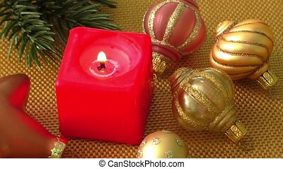 Burning candle in a Christmas setting with seasonal...