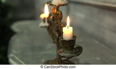burning candle in an old candle on the fireplace candelabra bright romantic, ancient traditional light illuminated closeup, style to beeswax, candlestick hot steel