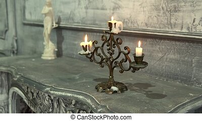 burning candle in an old candle on the fireplace candle antique fire, candleholder object retro burning flicker halloween. Shiny to decor hot steel