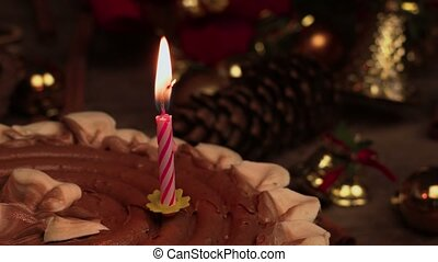 Burning candle in chocolate cake near Christmas decoration