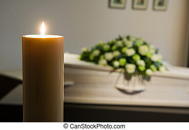 Burning candle in front of coffin - A burning candle with a...