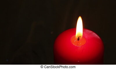 Burning candle in red wax on a dark background.