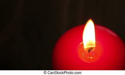 Burning candle in red wax on a dark background