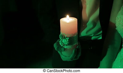 Burning candle in the hand of men in the dark. Slow motion shot.