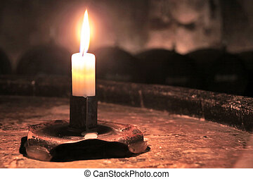 Burning candle in wine cellar