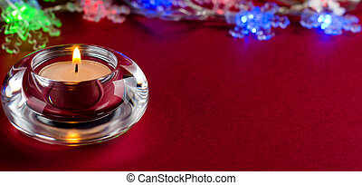 Burning candle on red background.